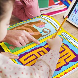preschool girl working on inside pages of workbook